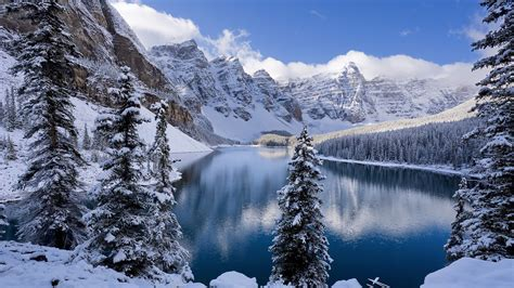 Winter, snow-covered mountains and trees, icy lake